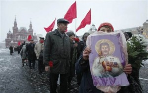 Russian Communists, one of them holding Stalin's poster, line up along the Red Square to mark 132nd birth  anniversary of Soviet dictator Josef Stalin in downtown Moscow, Russia, Wednesday, Dec. 21, 2011. The Central Historic Museum is at the background. (AP Photo/Misha Japaridze)